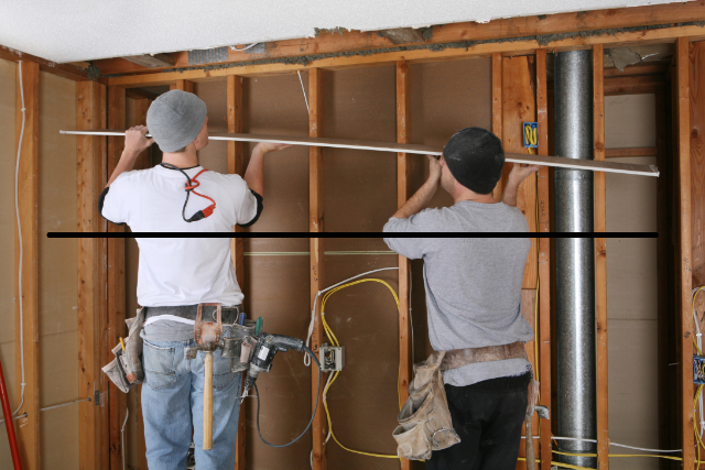 Bend drywall workers installing drywall