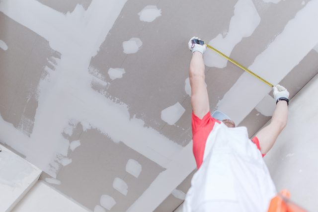Drywall Remodel with a worker on a ladder measuring the ceiling